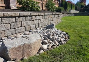 Retaining rock wall on beautifully landscaped lawn. Hardscape design services by Boulder Falls Landscape in Vancouver WA and Camas Washington