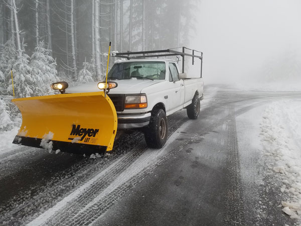 Snow plow truck driving on snowy road. Boulder Falls provides snow removal services in Vancouver WA and Camas WA.